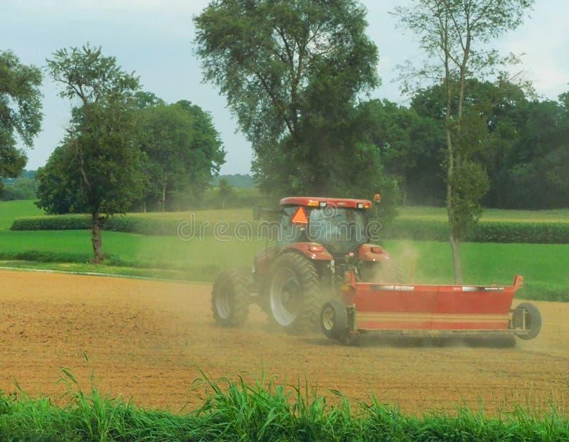 Un tractor que fertiliza un campo imagenes de archivo