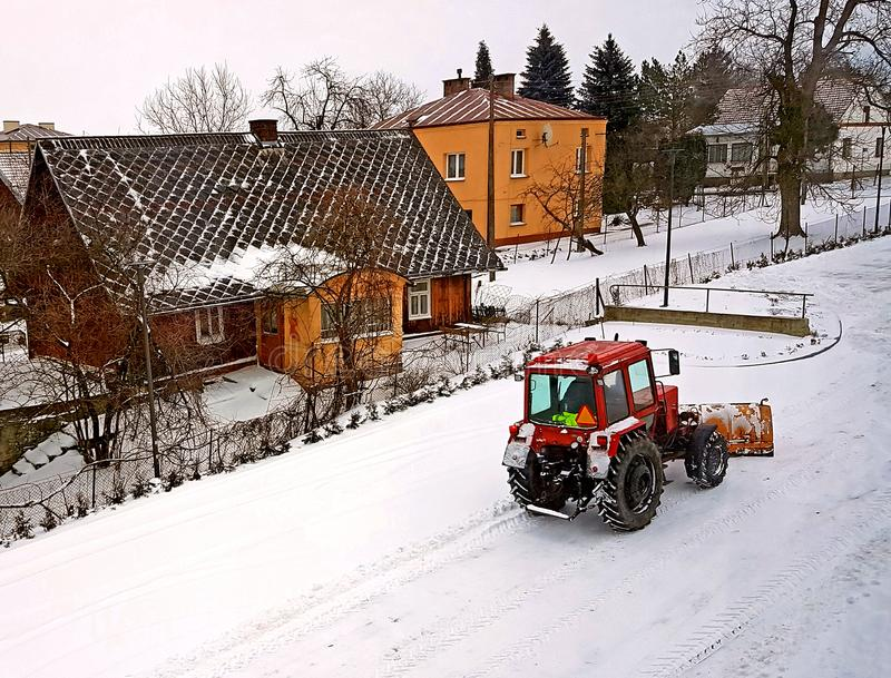 Un tractor rojo despeja el camino de la nieve Limpieza del invierno de la calle SERVICIO COMUNITARIO Tiempo Aldea del invierno sn imagen de archivo libre de regalías