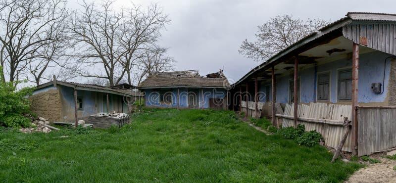 Un tradicional, abandonado yarda en un pueblo con la hierba crecida, durante verano en el Moldavia fotografía de archivo libre de regalías