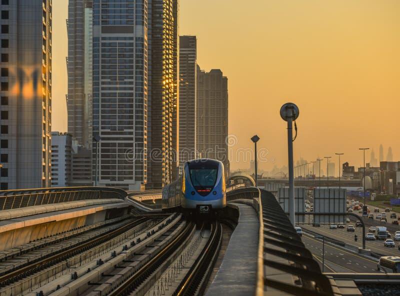 Un train de métro fonctionnant sur la voie au coucher du soleil photos stock