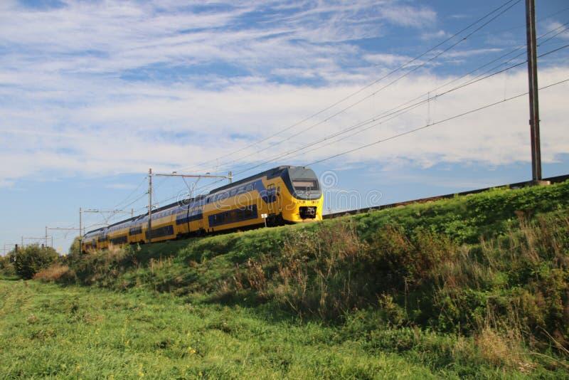 Un train interurbain de VIRM dans la voie ferrée sur le niveau de la mer dans le repaire aan IJssel de Nieuwerkerk image stock