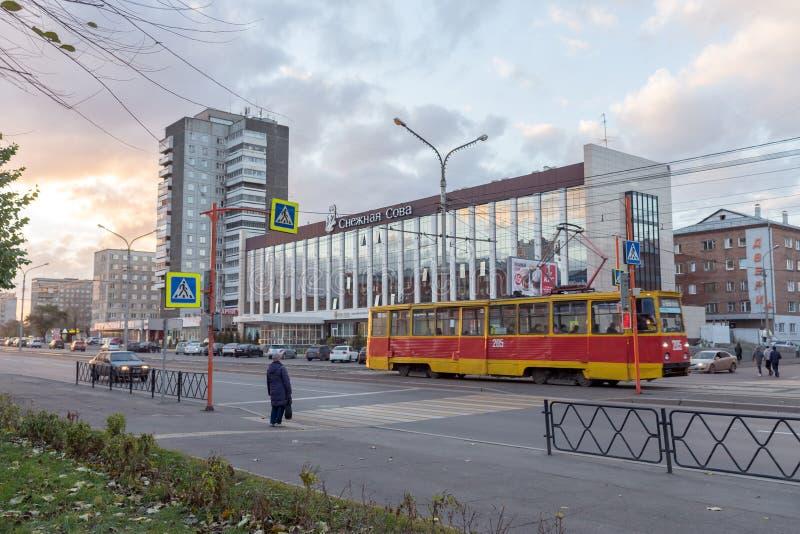 Un tram guida lungo il viale del lavoratore di Krasnojarsk contro lo sfondo di Owl Hotel bianco immagini stock libere da diritti