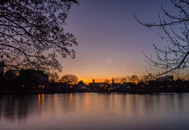Un tramonto di inverno sopra un lago ghiacciato fotografia stock libera da diritti