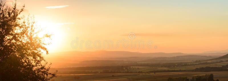Un tramonto lunatico sopra una catena montuosa, campi protetti in nebbia immagini stock libere da diritti