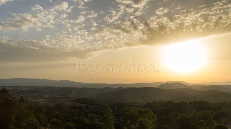 Un tramonto nebbioso nelle colline in Sardegna immagini stock