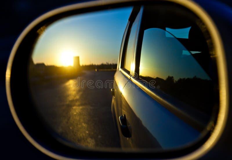 Un tramonto nello specchio di rearview dell'automobile immagine stock libera da diritti