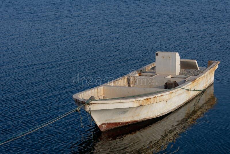 Un tramonto uguagliante con una barca di sguardo rustica che assorbe i raggi nell'acqua blu fotografia stock