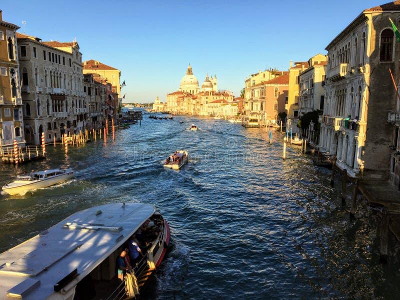 Un transbordador del agua y un viaje grandes del taxi del agua abajo de Grand Canal en un día de verano soleado en Venecia, Itali foto de archivo