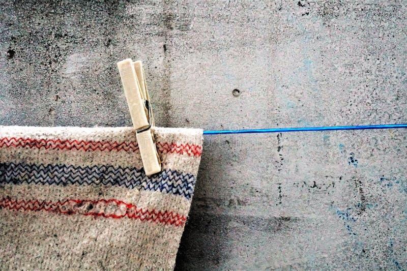 Un trapo en una cuerda con una pinza como tentativa en el fondo original imagen de archivo libre de regalías