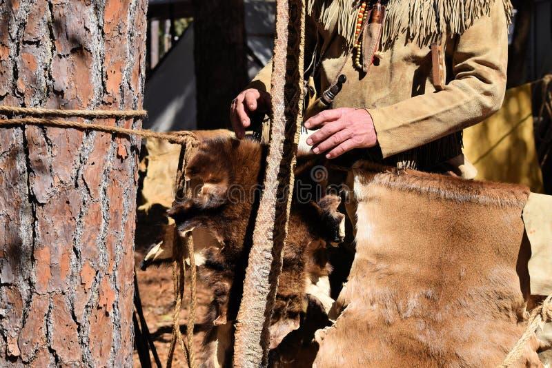 Un trappeur avec des fourrures, des peaux et la peau de serpent à sonnettes photo libre de droits