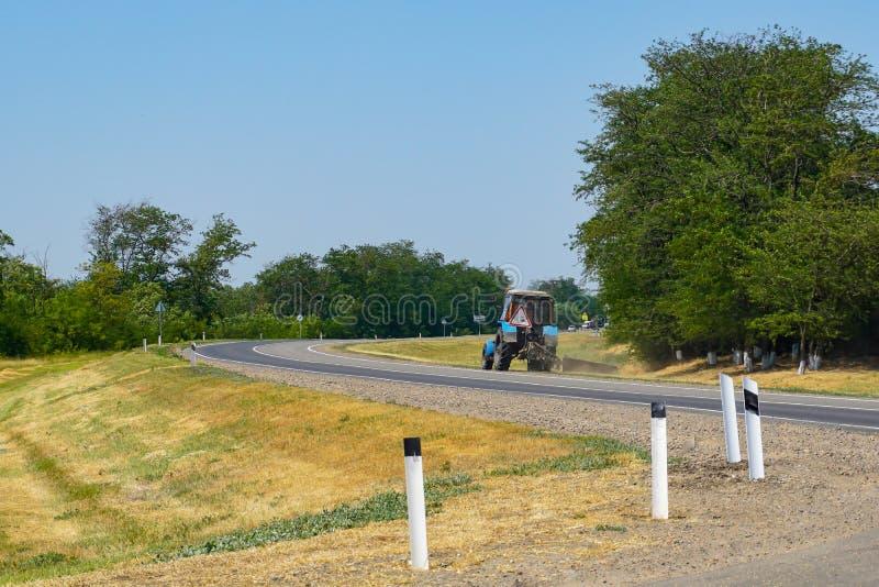 Un trattore falcia l'erba dal lato di una strada principale vicino ad un campo coltivare con grano immagine stock