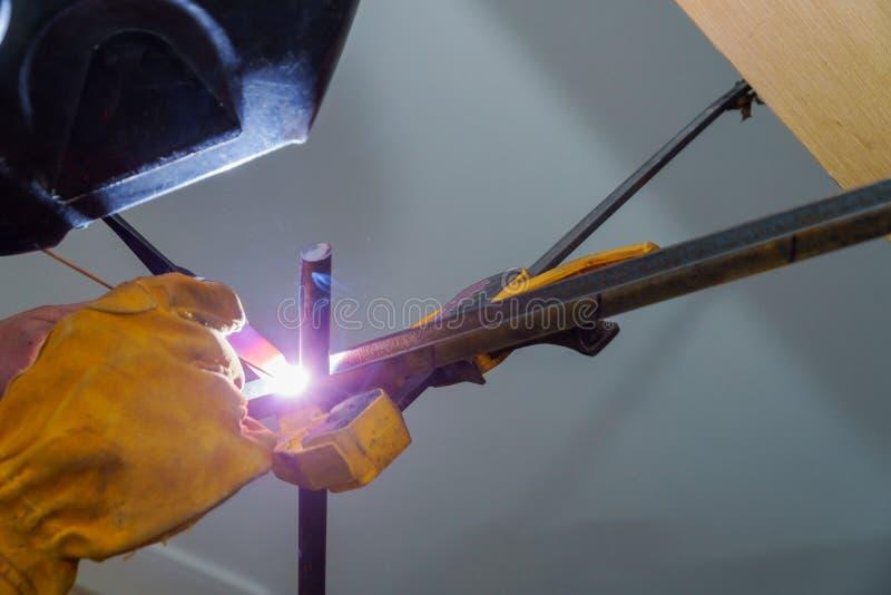Un travailleur avec des gants soude quelques balustrades photo libre de droits