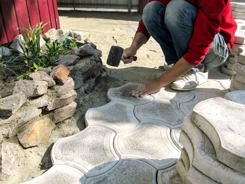 Un travailleur bat une surface du pav? figur? gris avec un maillet, le pla?ant dans un m?lange sec de sable-ciment Concept de photographie stock
