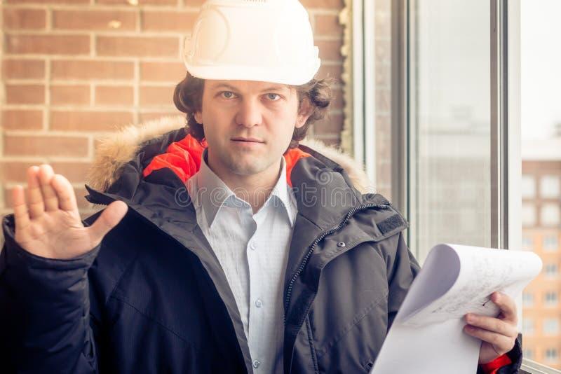 Un travailleur contrarié fâché de constructeur dans un casque avec des dessins de projet prévoit dans son un main et téléphone po images libres de droits