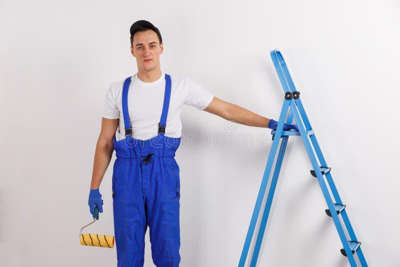 Un travailleur de la construction de sexe masculin, dans l'uniforme, se tient avec une main sur l'escabeau, tenant un rouleau de  images stock