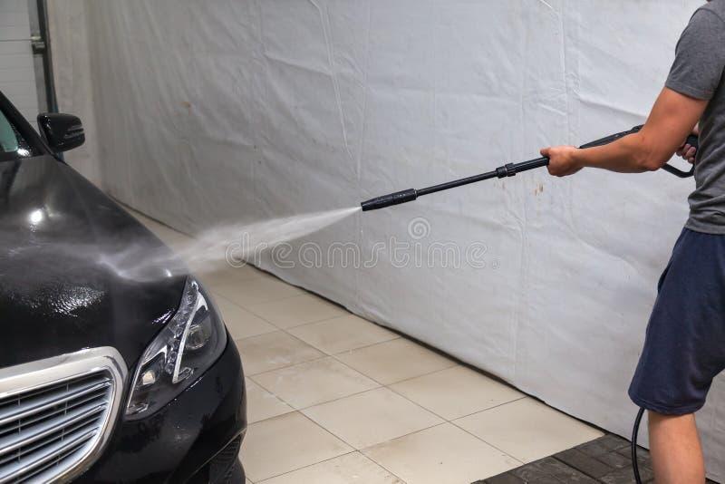 Un travailleur de sexe masculin lave le capot d'une voiture noire avec un appareil à haute pression de quels écoulements d'eau et images stock