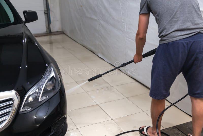 Un travailleur de sexe masculin lave une voiture noire avec un appareil à haute pression de quels écoulements d'eau et enlève la  images libres de droits