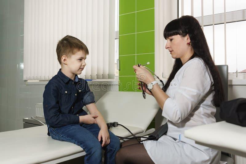 Un travailleur médical dispose un stéthoscope pour mesurer la pression de garçons images libres de droits