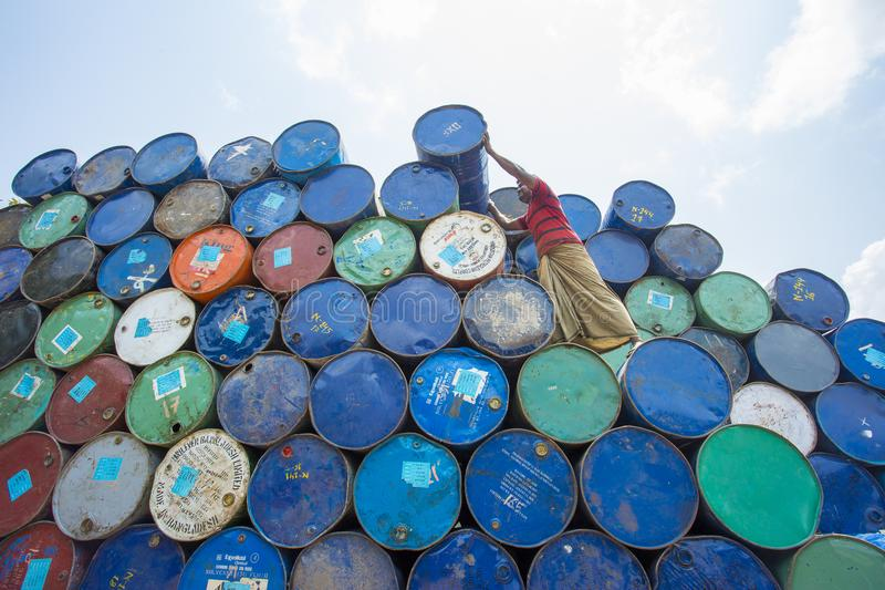Un travailleur organise des barils aux régions de Sadarghat de rivières de Karnafuli, Chitagong, Bangladesh photographie stock