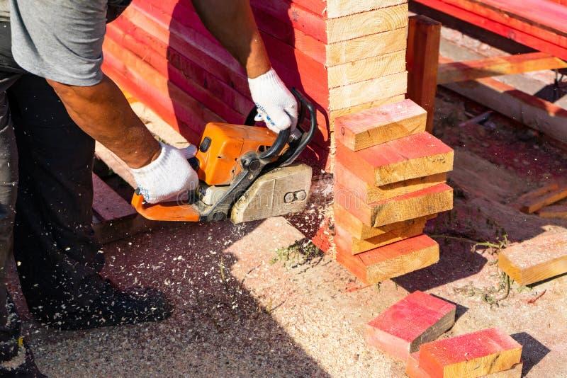 Un travailleur scie outre d'un panneau en bois de tronçonneuse Construction de Chambre photos libres de droits