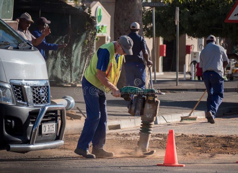 Un travailleur sud-africain de route utilise un compacteur de la terre photographie stock
