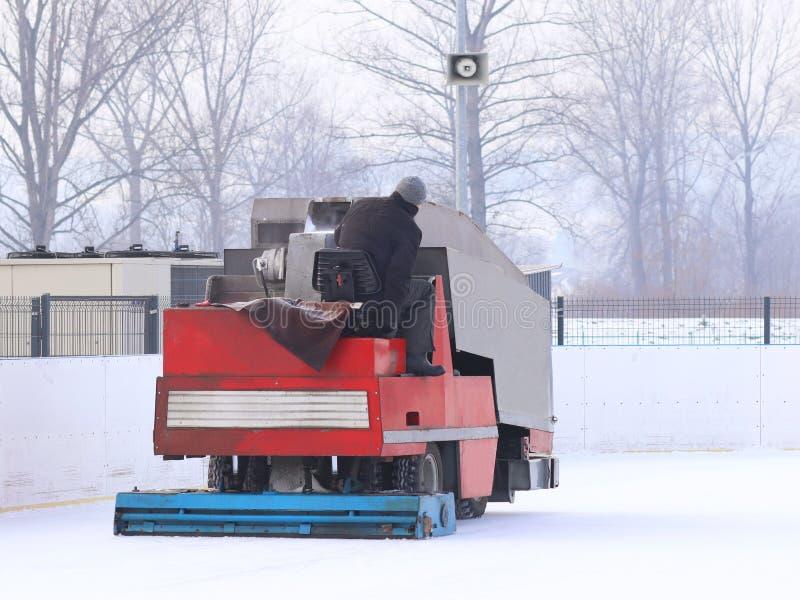 Un travailleur tire une glace spéciale la machine que maintenant à l'des sports patinent Cuisson de l'endroit pour le patinage pr photos libres de droits