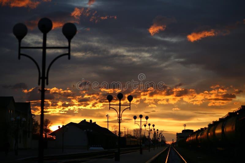 Un tren corre en las vías en la estación i durante una salida del sol hermosa imagenes de archivo