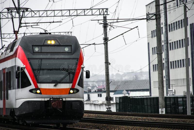 Un tren de pasajeros de alta velocidad viaja a lo largo de las líneas ferroviarias en la ciudad fotografía de archivo libre de regalías