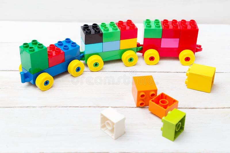 Un tren del juguete de cubos del lego en un fondo de madera educativo fotografía de archivo