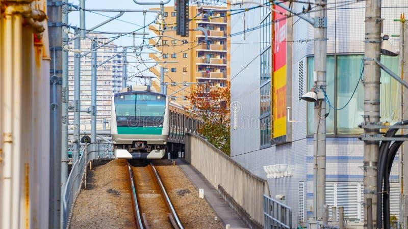 Un tren local llega la estación de Ikebukuro fotografía de archivo