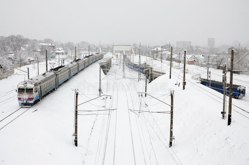 Un treno lungo delle carrozze ferroviarie sta muovendosi lungo la strada ferrata Paesaggio ferroviario nell'inverno dopo le preci fotografia stock libera da diritti