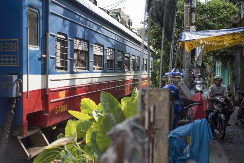 Un treno passa da una via minuscola con i motorini che guidano in Ho Chi Minh City, Vietnam fotografia stock libera da diritti