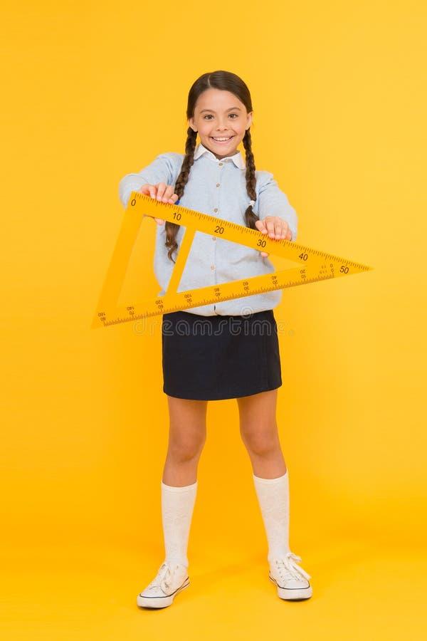 Un triángulo tiene tres lados y tres ángulos Triángulo feliz adorable de la tenencia del alumno en fondo amarillo Muchacha linda imagenes de archivo