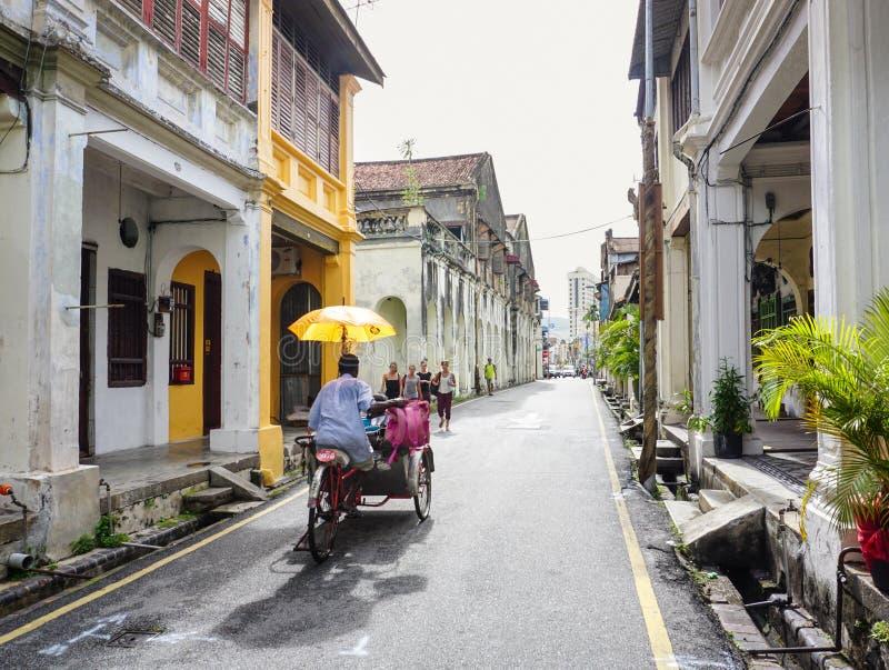 Un tricycle d'équitation d'homme sur la rue dans Melaka, Malaisie images libres de droits