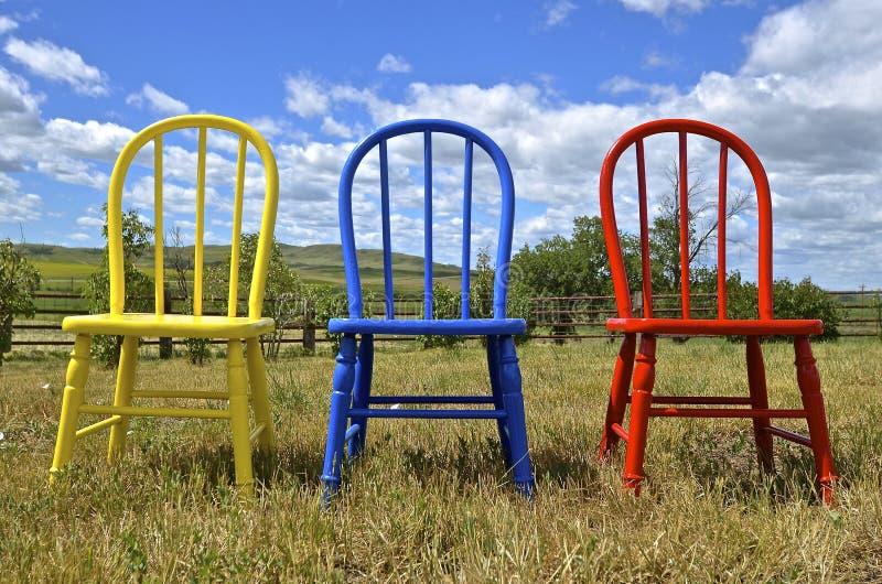 Un trio delle sedie di legno variopinte di Windsor in una regolazione all'aperto immagini stock libere da diritti