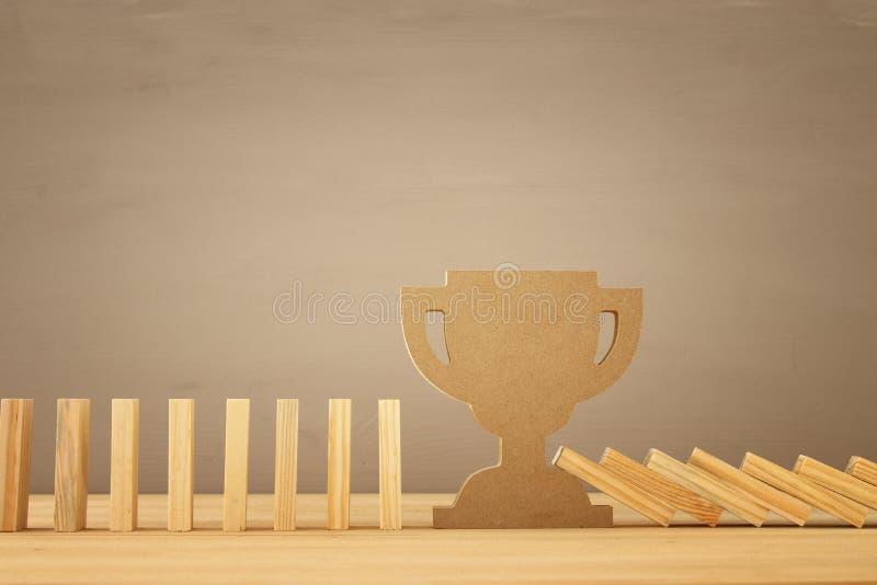 Un trofeo que para el efecto de dominó ejecutivo y concepto de control del riesgo fotos de archivo
