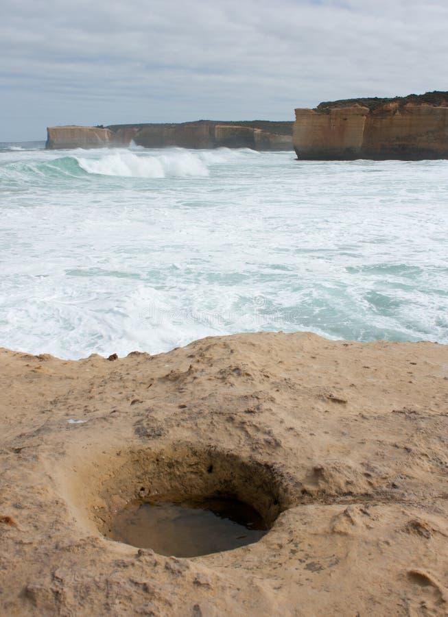 Un trou dans une roche international il premier plan et falaises dans la distance à la grande route d'océan en Australie images libres de droits