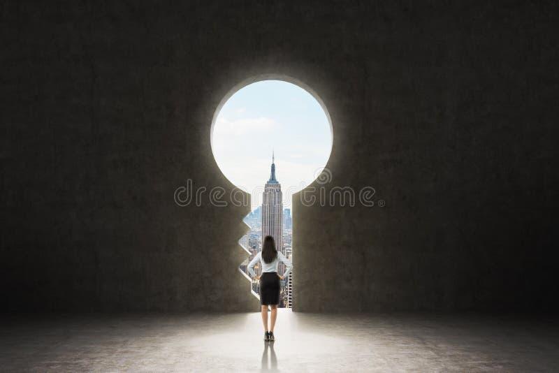 Un trou de la serrure dans le mur en béton Une dame d'affaires habillée dans le costume formel regarde New York City dans le trou photo libre de droits