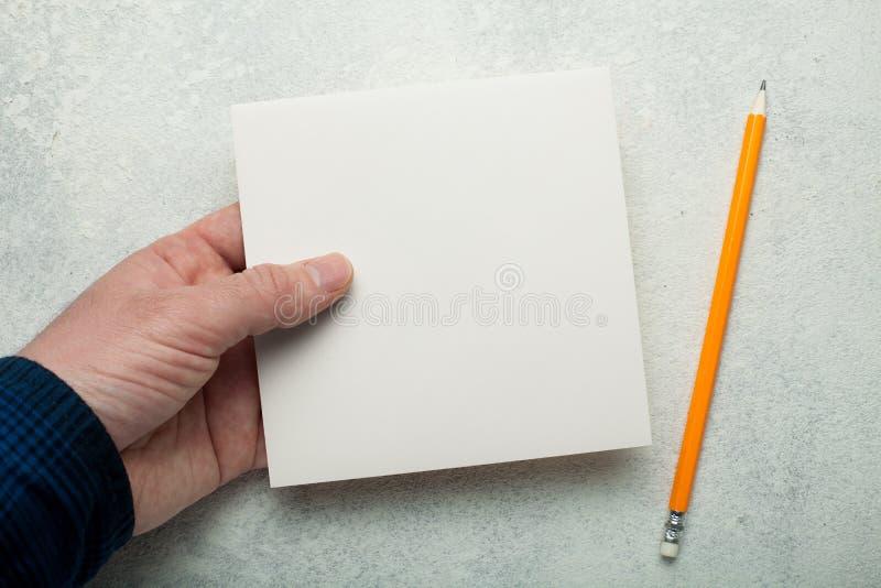 Un trozo de papel cuadrado vacío en la mano de un hombre, un lápiz amarillo al lado de ella Maqueta imagen de archivo