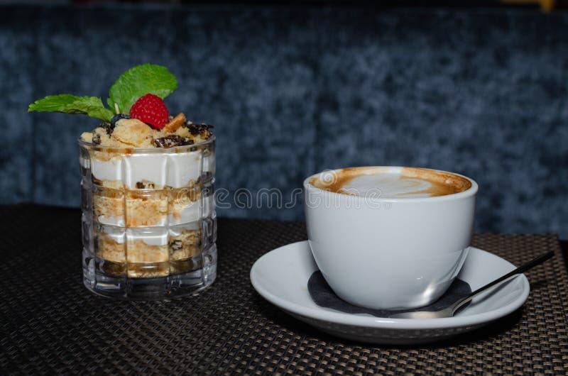 Un trozo de pastel de miel en un vaso y una taza de capuchino sobre una mesa oscura imagen de archivo