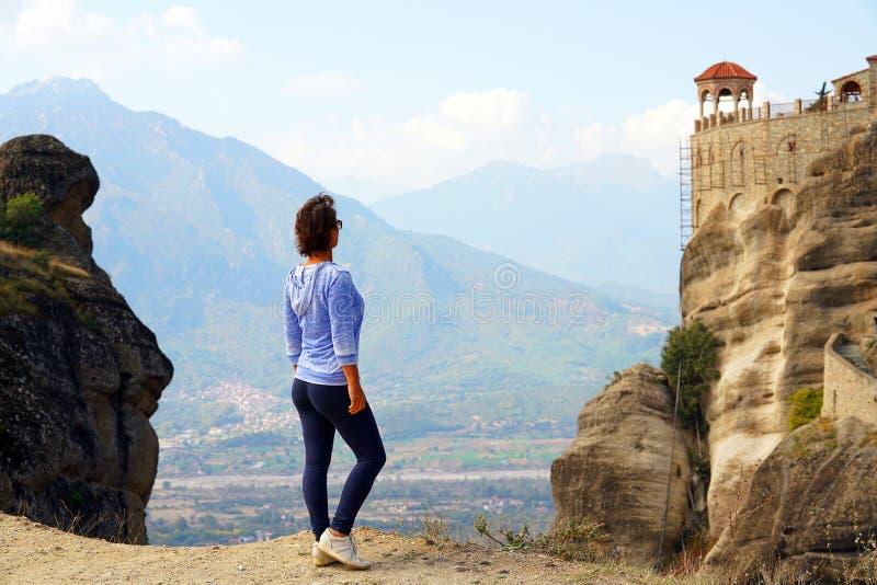 Un turista admira el paisaje hermoso de Meteora, Grecia con sus monasterios, sus montañas y su naturaleza fotografía de archivo