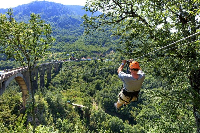 Un turista attraversa una cabina di funivia lunga sopra una montagna e una foresta attraverso Tiara River fotografie stock