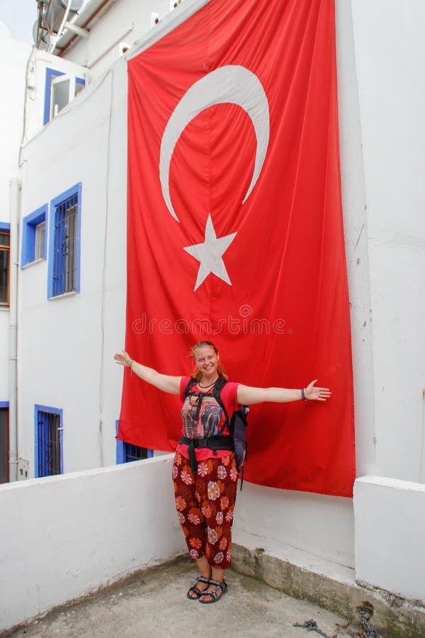 Un turista blanco de la chica joven en ropa roja con una mochila es permanente y sonriente contra la perspectiva de un edificio c imagen de archivo