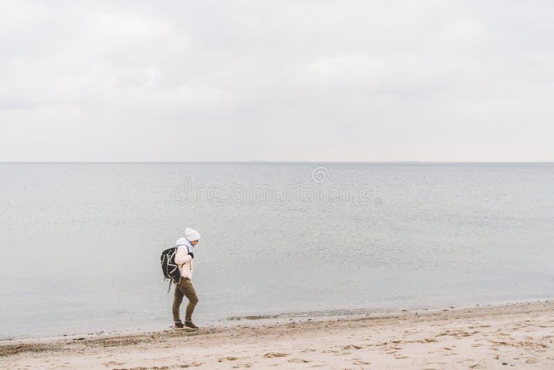 Un turista caucásico joven de la mujer del hombre caucásico con una mochila negra en una playa arenosa cerca del mar Báltico en i imagenes de archivo