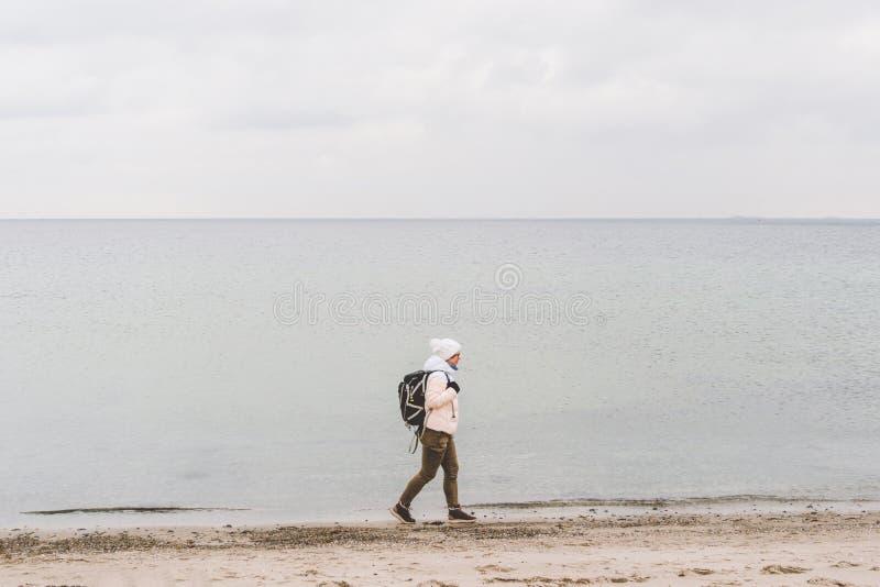 Un turista cauc?sico joven de la mujer del hombre cauc?sico con una mochila negra en una playa arenosa cerca del mar B?ltico en i fotos de archivo libres de regalías