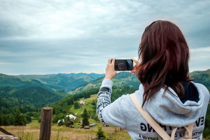 Un turista de la chica joven con una situación de la mochila encima de las fotografías de una montaña en un teléfono un paisaje d fotografía de archivo libre de regalías