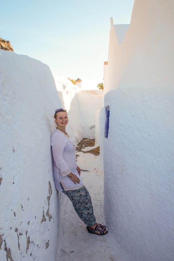 Un turista de la chica joven en las sonrisas blancas de la ropa y terraplenes en las paredes blancas de la ciudad de Fira imagen de archivo