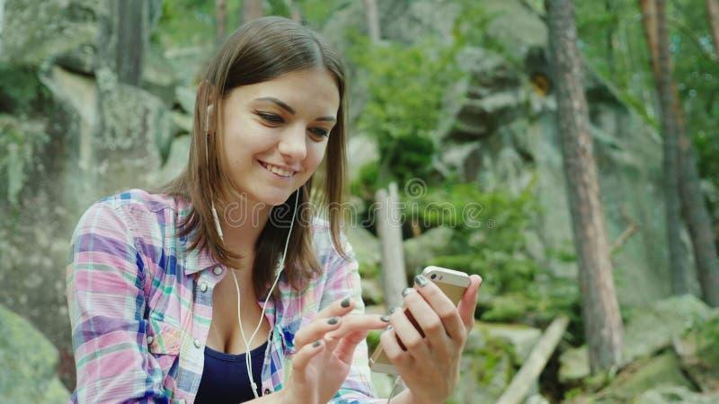 Un turista de la mujer joven utiliza un smartphone en un alza Sits que descansa contra las rocas en las montañas fotos de archivo