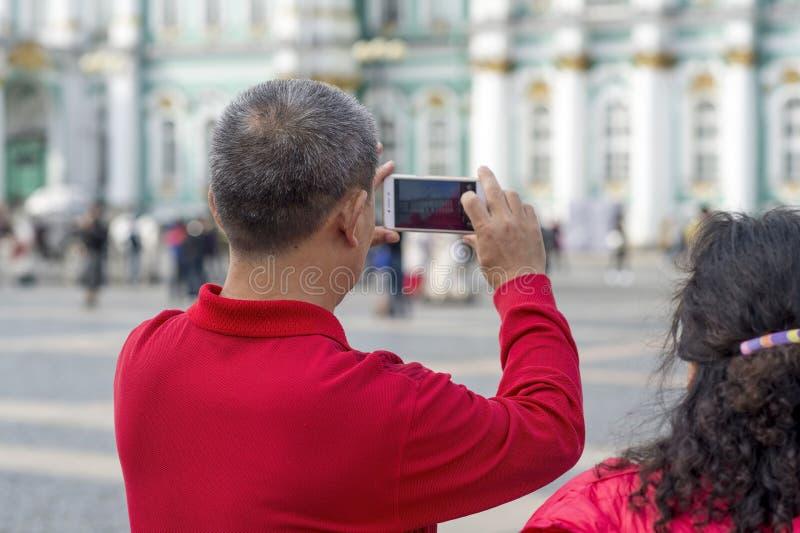 Un turista del hombre de las fotografías asiáticas del aspecto en un smartphone el edificio de la ermita en el cuadrado del palac fotografía de archivo