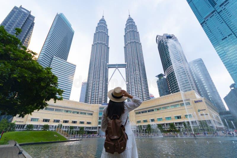 Un turista della donna sta facendo un giro turistico la torre gemella KLCC di Petronas in Kuala Lumpur immagine stock libera da diritti